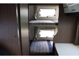 車両後方にある常時ダブルベッドです。ダブルベッドには、各ベッド収納スペースも完備しています。また、一段目ベッドの下にも収納スペースがあり、車両左側面・車両後方からアクセスも可能です。